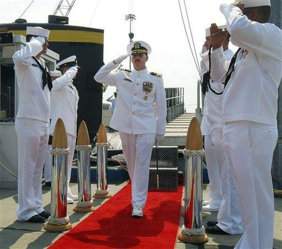 In this Aug. 3, 2012 photo provided by the U.S. Navy, Cmdr. Michael P. Ward II, center, is saluted during the change-of-command ceremony for the nuclear submarine USS Pittsburgh at the Naval Submarine Base New London, in Groton, Conn.  Ward was relieved of his command in August 2012 after he faked his own death to end an affair with a woman. Ward's lawyer said Friday, April 12, 2013, during a hearing in Groton to determine his status with the Navy, that Ward admits to the mistake and apologizes, and that he should not be expelled from the Navy. (AP Photo/U.S. Navy, Jason J. Perry ) Photo: AP / U.S. Navy