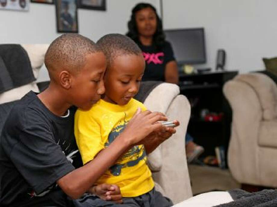 Cam'ron Richardson, left, plays a video game with his little brother, Anthony Richardson, right, as his mother watches, rear, at their home in Moore, Okla.