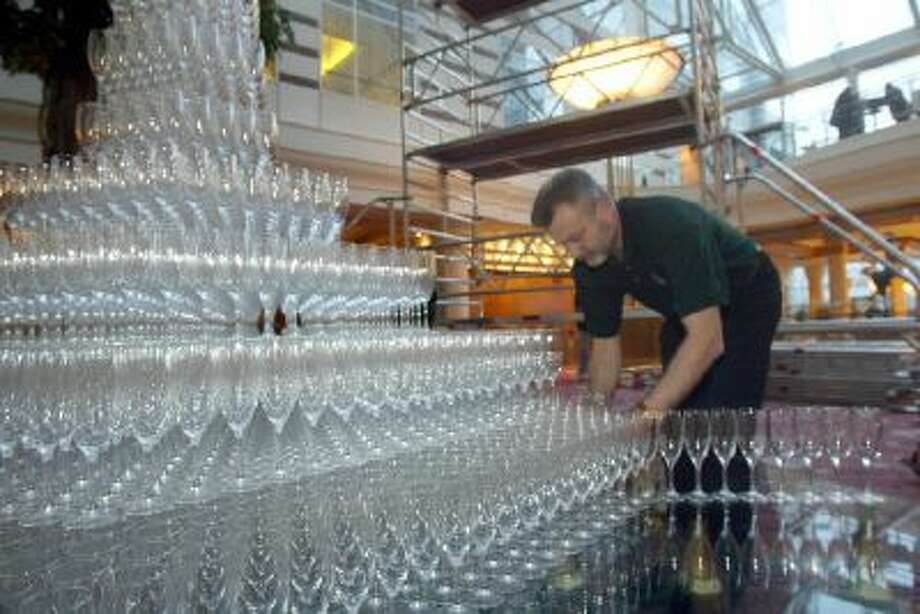 An employee of French champagne manufacturer Leclerc Briant stacks champagne flutes 08 February 2004 in Roissy in an attempt to break the Guiness World Record for the highest champagne fountain.