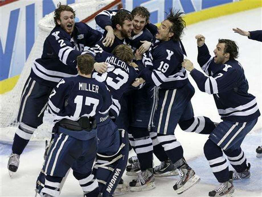 Yale goalie Jeff Malcolm (33) is swarmed by teammates after shutting out Quinnipiac 4-0 to win the NCAA men's college hockey Frozen Four national championship game in Pittsburgh, Saturday, April 13, 2013. (AP Photo/Gene Puskar) Photo: ASSOCIATED PRESS / AP2013