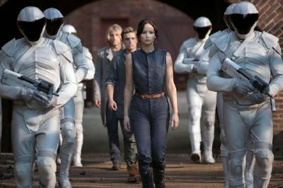 Katniss Everdeen (Jennifer Lawrence), Peeta Mellark (Josh Hutcherson) and Haymitch Abernathy (Woody Harrelson) in 'The Hunger Games: Catching Fire.'