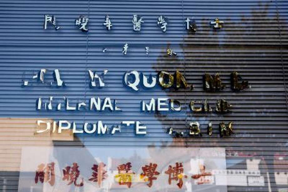 Dr. Hew Wah Quon's name is half-peeled off the front window of his office in the Chinatown neighborhood of Los Angeles, Calif.