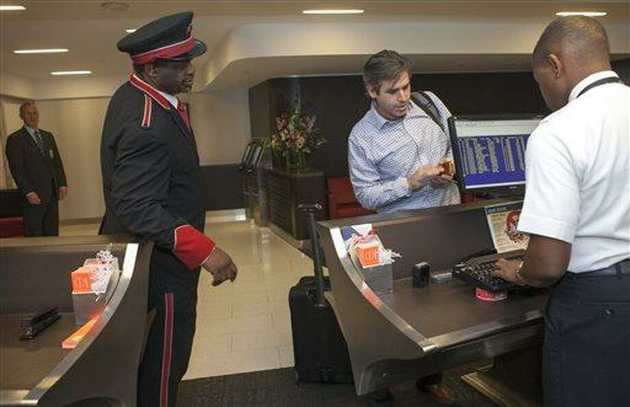 In this Thursday, March 14, 2013 photo, American Airlines skycaps Alex Abel Gonzalez, left, and Frederick Pearson await outside the AA Flagship lounge at Los Angeles International Airport, LAX. American's Flagship Check-in service, a VIP discreet and expedited check-in process offers personal access to agents for assistance with check-in and bag check, and a separate security line when flying through LAX and now Miami International Airport. (AP Photo/Damian Dovarganes) Photo: AP / AP