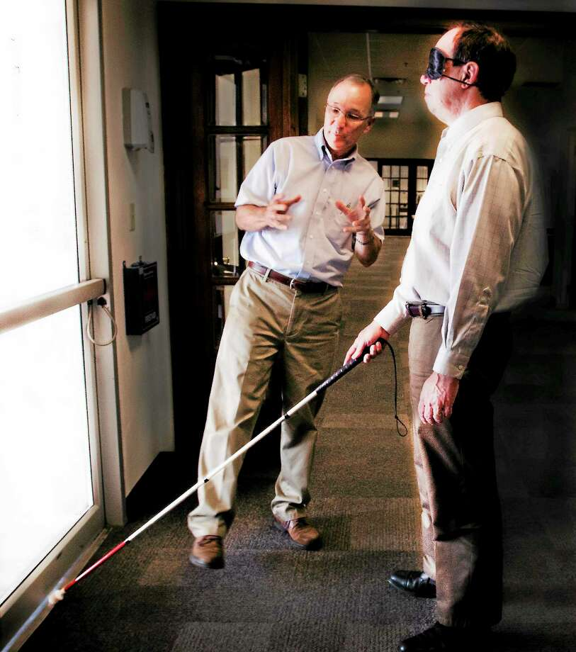 Melanie Stengel — Register       John Waiculonis (L) guides reporter Ed Stannard as he learns how to navigate a doorway while blindfolded 8/20. Photo: Journal Register Co.