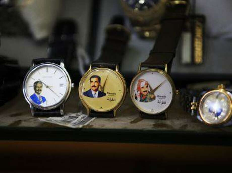 In this Sunday, April 7, 2013 photo, watches with image of the former dictator Saddam Hussein are on display at a souvenirs shop in downtown Baghdad, Iraq. Ten years ago, a statue fell in Paradise Square. Joyful Iraqis helped by a U.S. Army tank retriever pulled down their longtime dictator, cast as 16 feet of bronze. The scene broadcast live worldwide became an icon for a war, a symbol of final victory over Saddam Hussein. But for the people of Baghdad, it was only the beginning. The toppling of the statue on April 9, 2003, remains a potent symbol that has divided Iraqis ever since. (AP Photo/ Karim Kadim) Photo: AP / AP