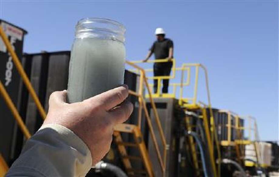 A jar holding waste water from hydraulic fracturing is held up to the light at a recycling site in Midland, Texas. The drilling method known as fracking uses huge amounts of high-pressure, chemical-laced water to free oil and natural gas trapped deep in underground rocks. With fresh water not as plentiful companies have been looking for ways to recycle their waste. Photo: AP / AP