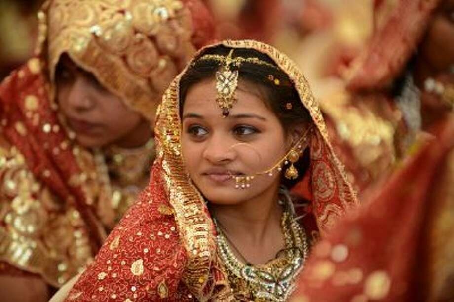 An Indian Muslim bride is decked out in gold jewelry during a mass wedding ceremony. Photo: AFP/Getty Images / 2013 AFP