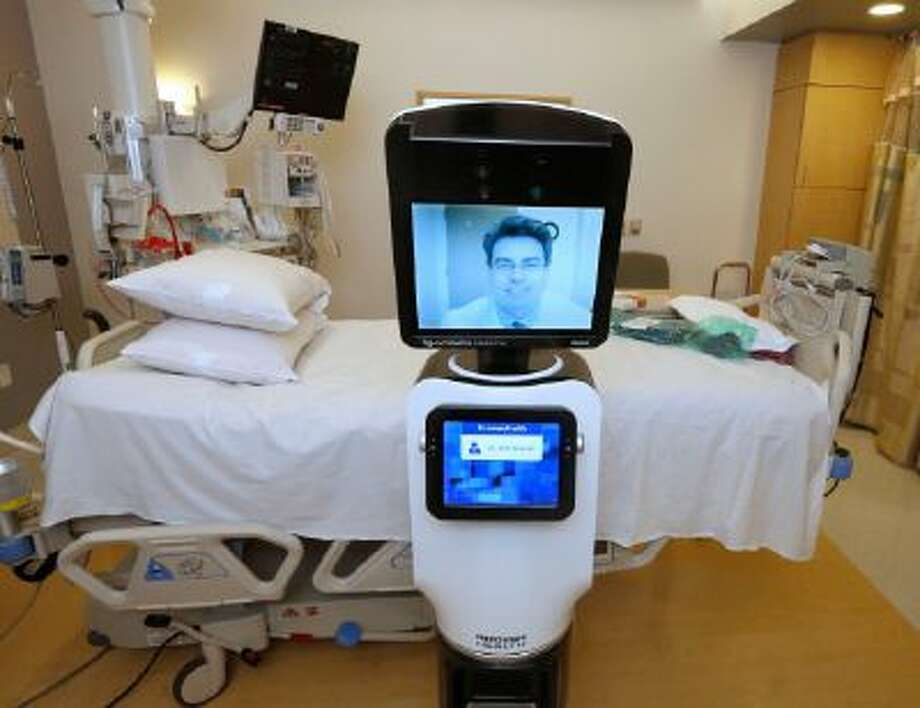 "In this photo taken Wednesday, Nov. 6, 2013, Dr. Alan Shatzel, medical director of the Mercy Telehealth Network, is displayed on the monitor RP-VITA robot at Mercy San Juan Hospital in Carmichael, Calif. The robots enable physicians to have a different bedside presence as they ""beam"" themselves into hospitals to diagnose patients and offer medical advice during emergencies."
