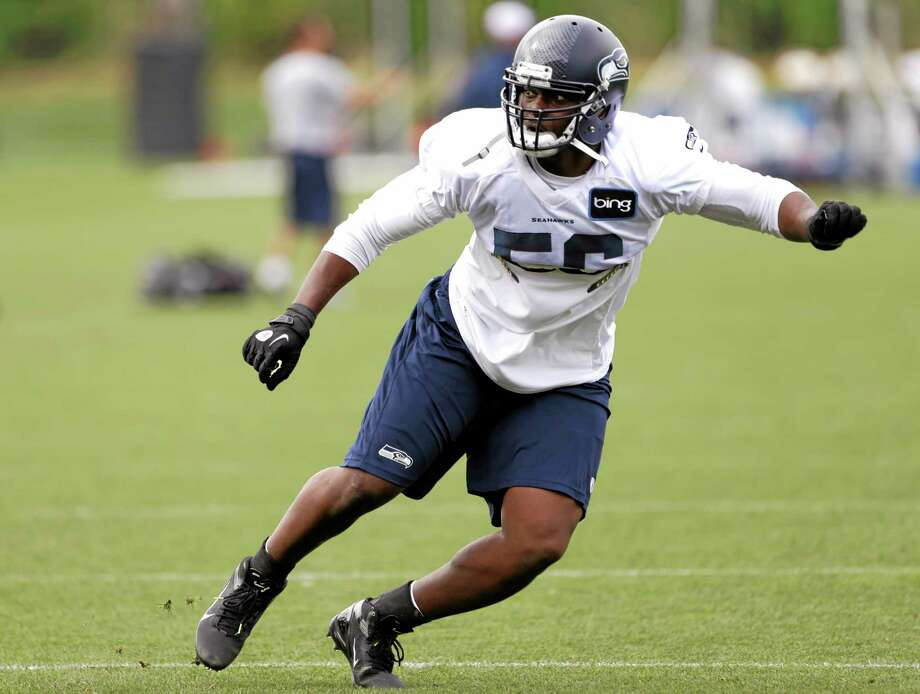 Seattle Seahawks' Cliff Avril runs through a drill at an NFL football training camp Wednesday, Aug. 14, 2013, in Renton, Wash. (AP Photo/Elaine Thompson) Photo: AP / AP