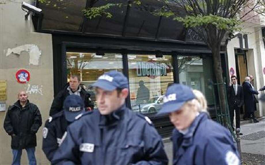 Police officers stand outside Liberation newspaper office in Paris, Monday, Nov. 18, 2013, after a gunman opened fire in the lobby, wounding a photographer's assistant before fleeing. Fabrice Rousselot, editor of the daily newspaper Liberation said the 27-year-old victim was in serious condition. (AP Photo/Thibault Camus) Photo: AP / AP