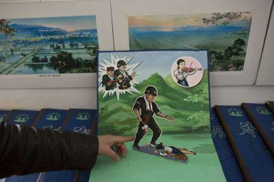 A North Korean teacher opens a children's pop-up book depicting a U.S. soldier killing a Korean woman with a hatchet, March 9, at Kaeson Kindergarten in central Pyongyang. For North Koreans, the systematic indoctrination of anti-Americanism starts as early as kindergarten. Photo: ASSOCIATED PRESS / A2013