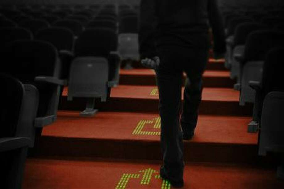 In this computer-generated image made available by Royal Philips NV, an LED sign in a carpet indicates a safety exit in a fictional cinema environment. Photo: AP / Philips