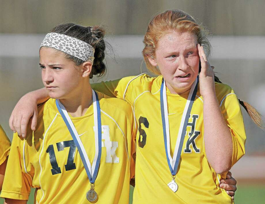 Haddam-Killingworth junior Molly Madore, at left comforts senior captain Gwendolyn Plum after their 1-0 loss to Waterford in the CIAC Class M State Girls Soccer Championship game at Rosek-Skubel Stadium at Middletown High School Saturday morning. Photo: Catherine Avalone — The Middletown Press  / TheMiddletownPress
