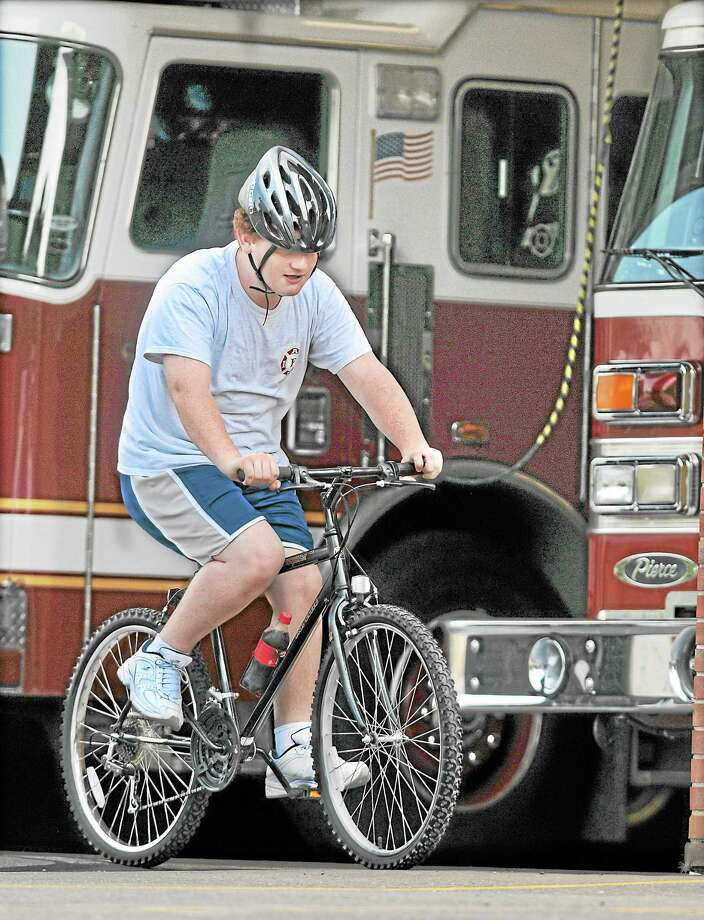 Middletown resident Joseph Pizzo, 18, takes off on a Black River Canyon, a bike loaned to him by Lt. Jonathan Handley while Lt. Anthony Lancia at South Fire District continues to repair Pizzo's bike. Pizzo, who has Asperger's Syndrome has spent five years hanging out at the fire station on Randolph Road. (Catherine Avalone — The Middletown Press) Photo: Journal Register Co. / TheMiddletownPress