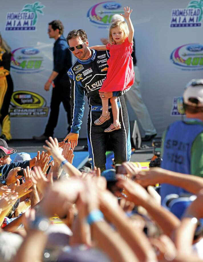 Jimmie Johnson with his daughter, Genevieve, greet fans during driver introductions before the NASCAR Sprint Cub Series race in Homestead, Fla., on Sunday. Photo: J Pat Carter — The Associated Press  / FR60642 AP