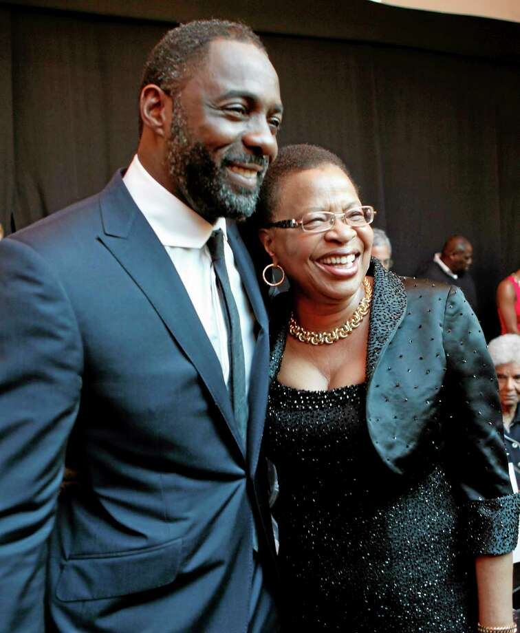 British Actor Idris Elba, left, who stars as Nelson Mandela, with Graca Machel, wife of former president Nelson Mandela, at the South African premier of the film Mandela - Long Walk To Freedom, in Johannesburg, Sunday Nov. 3, 2013. The biographical film directed by Justin Chadwick, is based on South African President Nelson Mandela's autobiography of the same name, which chronicles his early life, coming of age, education and 27 years in prison before becoming President and working to rebuild the country's once segregated society.  (AP Photo/Denis Farrell) Photo: AP / AP