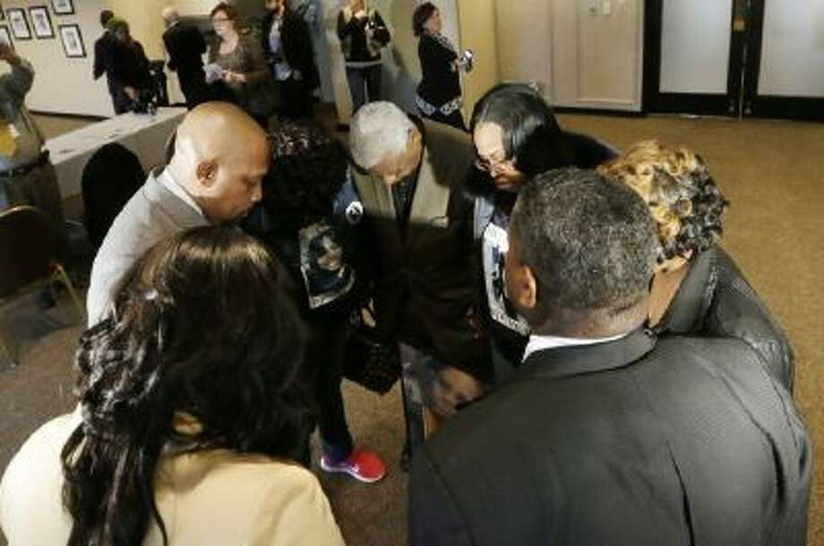 Family members and friends of Walter Ray Simmons and Monica McBride, the parents of Renisha McBride, pray at the conclusion of the news conference in Southfield, Mich., Friday, Nov. 15, 2013 where they responded to Wayne County Prosecutor Kym Worthy's decision announcement in the shooting death of their daughter Renisha McBride.