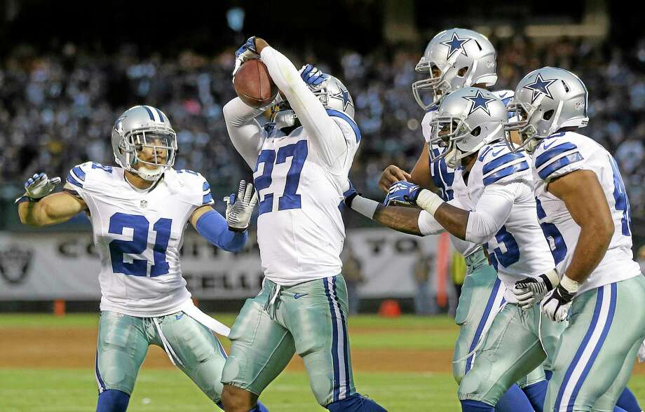 Dallas Cowboys defensive back J.J. Wilcox (27) celebrates with cornerback Sterling Moore (21) and teammates after intercepting a pass from Oakland Raiders quarterback Terrelle Pryor during the second quarter of an NFL preseason football game in Oakland, Calif., Friday, Aug. 9, 2013. (AP Photo/Marcio Jose Sanchez) Photo: AP / AP