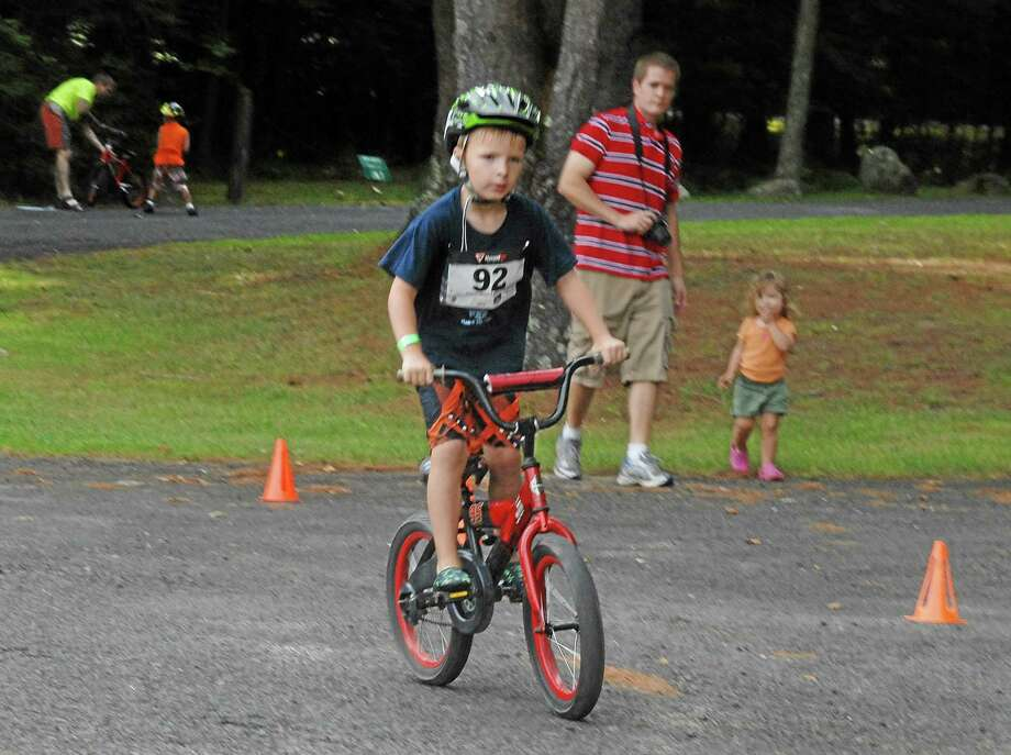 In this 2012 file photo provided by the Kowalski family, Chase Kowalski bikes during the 2012 Kids Who Tri Succeed Triathlon in Mansfield, Conn. Chase Kowalski loved to race, whether it was running, swimming or riding his bike. The 7-year-old, one of 26 people killed last Dec. 14 inside the Sandy Hook Elementary school, ran competitively for the first time when he was just 2½ years old. His parents decided to honor Chase's memory by a starting a foundation, raising money for children's fitness projects, family wellness and preschool education scholarships. (AP Photo/Kowalski family) Photo: AP / Kowalski Family