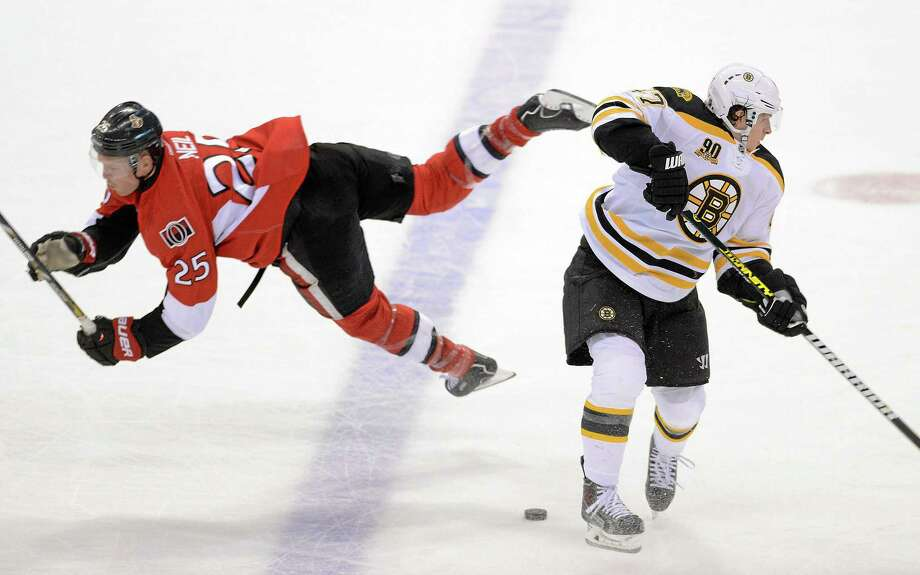 The Senators' Chris Neil, left, falls after a collision with the Boston Bruins' Torey Krug during the first period of Friday night's game in Ottawa, Ontario. Photo: Sean Kilpatrick — The Canadian Press  / The Canadian Press