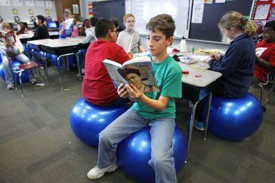 Evan Holmes reads a book while seated on an exercise ball in Sara Wright's fifth-grade classroom Wednesday, November 14, 2012, at Wea Ridge Elementary School near Lafayette, Ind. Wright wrote a grant to replace her classroom chairs with the balls. (AP Photo/Journal & Courier, John Terhune) MANDATORY CREDIT; NO SALES Photo: AP / Journal & Courier