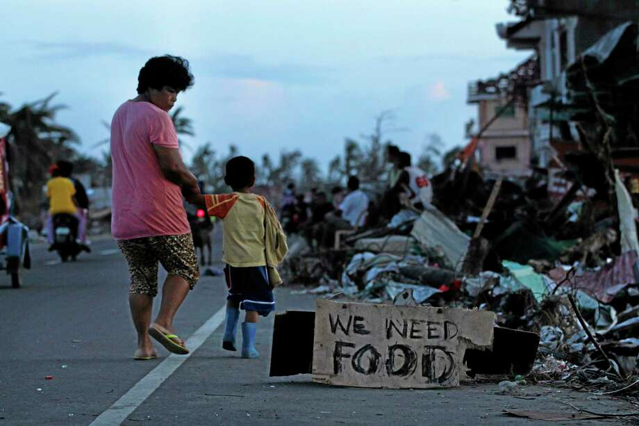 A mother notices a plea for food as she walks with her son past decimated neighborhoods from Typhoon Haiyan in Tacloban, central Philippines, Friday. Photo: Wally Santana — The Associated Press     / AP