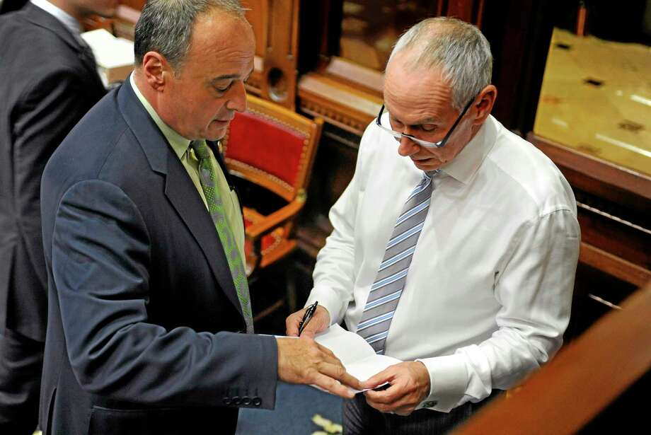 House Minority Leader Larry Cafero, R-Nowalk, left, speaks with Gov. Dannel P. Malloy's Chief of Staff Mark Ojakian, right, during the final day of session at the Capitol in Hartford, Conn., Wednesday, June 5, 2013.  Lawmakers wrap up a session that was dominated at the beginning and the end by issues related to the shooting at Sandy Hook Elementary School. (AP Photo/Jessica Hill) Photo: AP / FR125654 AP