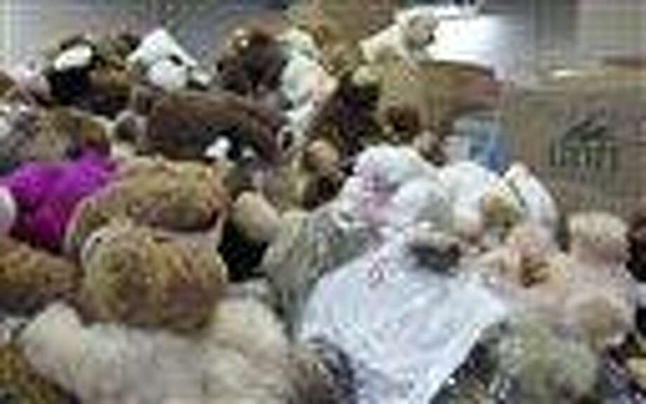 FILE - In this Monday, Dec. 31, 2012 file photo, piles of stuffed animals donated after 26 people were shot to death at Sandy Hook Elementary School, await sorting in a warehouse in Newtown, Conn.  Newtown officials and families of those killed have given away 63,790 stuffed animals and thousands of other gifts that poured into the town in the weeks following the massacre. The final boxes of toys and school supplies were shipped out of the warehouse on March 29, 2013.    (AP Photo/Pat Eaton-Robb) Photo: AP / AP