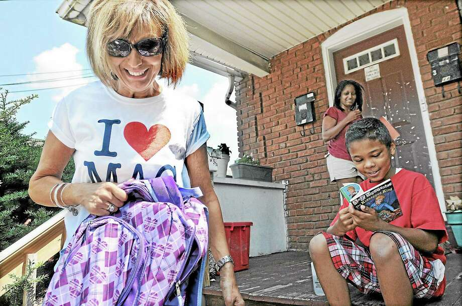 Rising third grader Treyvon Belin, 8, flips through a book he received from kindergarten teacher Angela Spaman during the Neighborhood Walk Wednesday afternoon in the Macdonough Elementary School district. The group of teachers found Treyvon sitting on the porch of the home of his friend and schoolmate Amarion Brown, who was inside finishing his lunch. Amarion's mother, Yesenia Anthony, is in the background. Catherine Avalone — The Middletown Press Photo: Journal Register Co. / TheMiddletownPress
