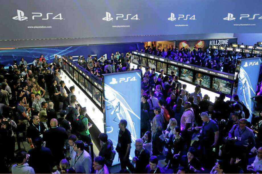"""FILE - In this June 11, 2013 file photo, show attendees play video games on the new Sony PlayStation 4 at the Sony booth during the Electronic Entertainment Expo, in Los Angeles. Twitch is coming to the PlayStation 4; the popular streaming video service that allows gamers to broadcast footage online was previously announced as a feature for Microsoft's Xbox One. Sony said Tuesday, Aug. 20, 2013, the service would also be available on the PS4, which adds a """"Share"""" button to its new controller. (AP Photo/Jae C. Hong, File) Photo: AP / AP"""