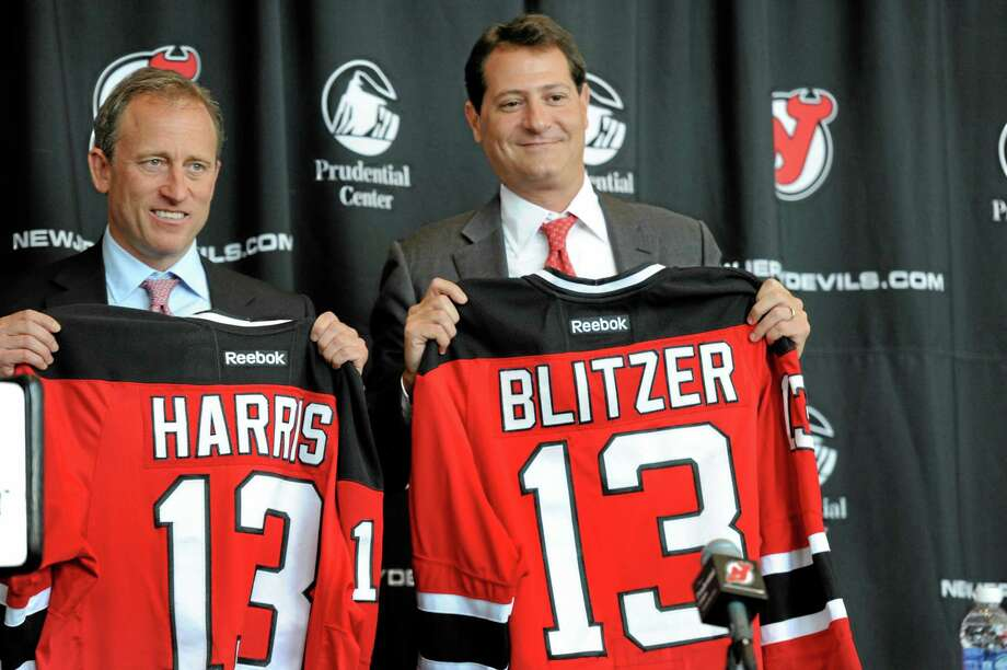 Joshua Harris, left, and David Blitzer, new owners of the New Jersey Devils NHL hockey team, hold up jerseys during a news conference Thursday, Aug. 15, 2013, in Newark, N.J. Harris and Blitzer are leaders of an investment group that bought the team. (AP Photo/Northjersey.com, Amy Newman)  MAGS OUT; TV OUT; INTERNET OUT; NO ARCHIVING; MANDATORY CREDIT  EDITORIAL USE ONLY Photo: AP / Northjersey.com