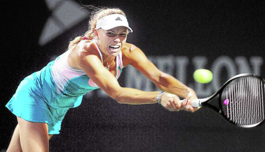 Caroline Wozniacki hits a backhand to Shuai Peng in a first-round match at the New Haven Open on Monday. Photo: Arnold Gold — Register