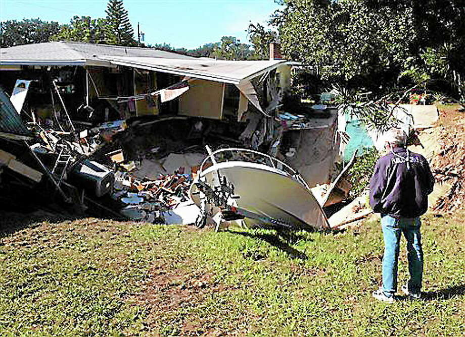 A man observes a sinkhole has swallowed parts of two houses in Dunedin, Fla. on Thursday, Nov. 14, 2013.  Dunedin Deputy Fire Chief Trip Barrs said the hole appeared to be about 12-feet wide when officials arrived on the scene. Residents of the neighboring houses also were evacuated as a precaution.  There are no reports of injuries. (AP Photo/The Tampa Tribune, Luke Johnson) Photo: AP / The Tampa Tribune