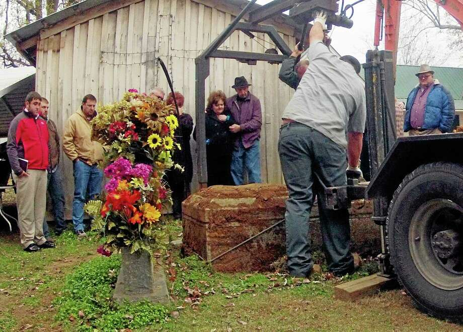 James Davis, right,  and relatives watch as his wife Patsy's body is exhumed from his front yard  Friday, Nov. 15, 2013 in Stevenson,  Ala. Davis lost a four-year court fight with the city to keep the remains of his wife outside his log home.  (AP Photo/Hal Yeager) Photo: AP / FR170776 AP