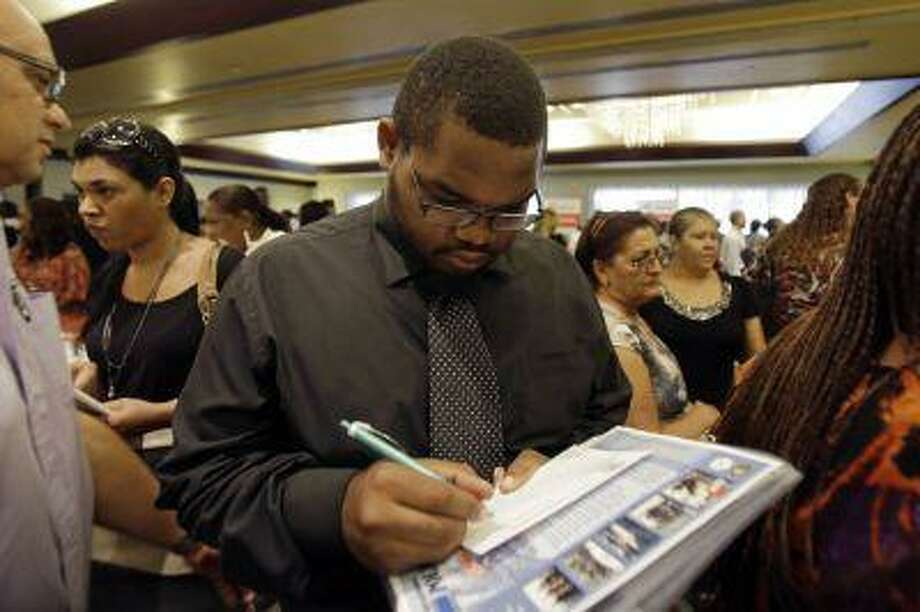 In this Wednesday, Aug., 14, 2013, photo, job seeker Kelsey Devoe, of Miramar, Fla., fills out a contact form at a job fair in Miami Lakes, Fla. The Labor Department reports on the number of Americans who applied for unemployment benefits last week on Thursday, Aug. 15, 2013. (AP Photo/Alan Diaz) Photo: AP / AP