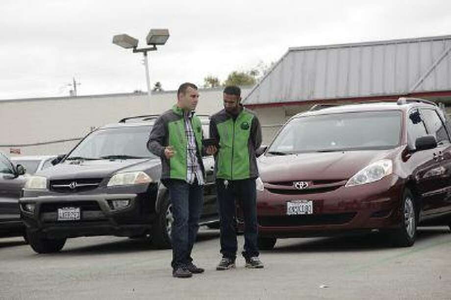 Andrei Parenco and Harun Ghori look over their inventory of available cars at FlightCar in Millbrae, Calif. on Wednesday, Aug. 7, 2013. FlightCar is a car-sharing service that allows travelers to leave their cars in a parking lot so that others can rent it while they are gone. Photo: San Jose Mercury News / San Jose Mercury News