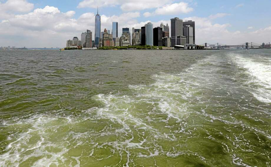 Lower Manhattan is visible from the Staten Island Ferry, in New York's Upper Bay, Tuesday, June 11, 2013. Giant removable floodwalls would be erected around lower Manhattan, and levees, gates and other defenses would be built elsewhere around the city under a nearly $20 billion plan proposed Tuesday by Mayor Michael Bloomberg to protect New York from storms and the effects of global warming. (AP Photo/Richard Drew) Photo: AP / AP