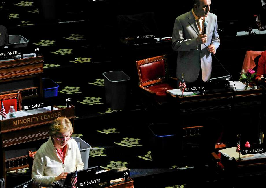 State Rep. Selim Noujaim, R-Waterbury, right, speaks as State Rep. Pam Sawyer, R-Bolton, left, works at her desk, during the final day of session at the Capitol in Hartford, Conn., Wednesday, June 5, 2013.  Lawmakers wrap up a session that was dominated at the beginning and the end by issues related to the shooting at Sandy Hook Elementary School. (AP Photo/Jessica Hill) Photo: AP / FR125654 AP