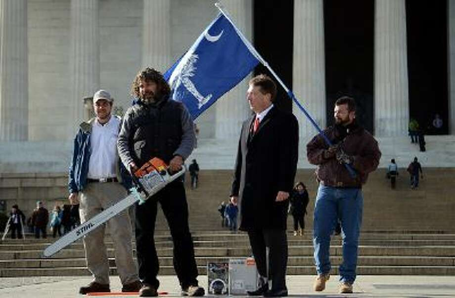 Chris Cox, second from left, the South Carolinian who became famous during the shutdown for singlehandedly mowing the lawn of the Lincoln Memorial, is presented a chainsaw from Kendall Almerico of STIHL, the 'world's leading chainsaw manufacturer.' Photo: The Washington Post/Getty Images / 2013 The Washington Post