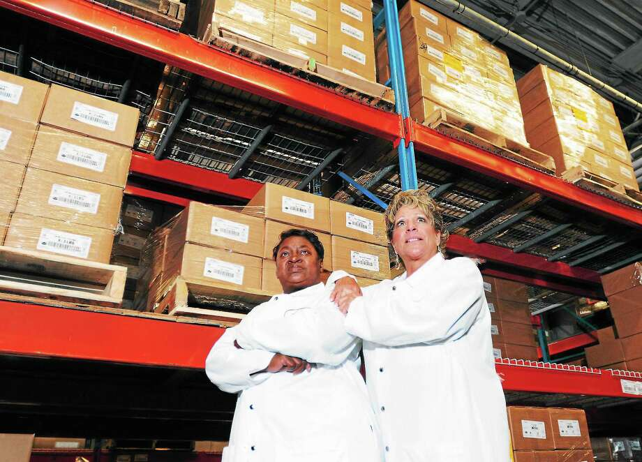 Hummel Brothers office administrators Mary Wilson, left, and Marisa Pepe stand in a walk-in cooler with Hummel Brothers packaged meat products in the company's New Haven warehouse Tuesday. Wilson and Pepe detected a phone call scam this summer from individuals posing as representatives of United Illuminating claiming false payment claims, saying power would be shut off the Hummel Brothers company. Photo: Peter Hvizdak — Register   / ©Peter Hvizdak /  New Haven Register