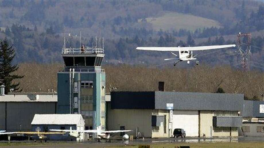 FILE - In this March 7, 2013 file photo, a small plane takes off past the control tower at Troutdale Airport in Troutdale, Ore. Starting this weekend, control towers at scores of small airports are to begin shutting down because of government-wide automatic spending cuts. But federal officials insist the closures won't compromise safety, and there's evidence that some of the closures may even make economic sense. (AP Photo/Don Ryan) Photo: AP / AP