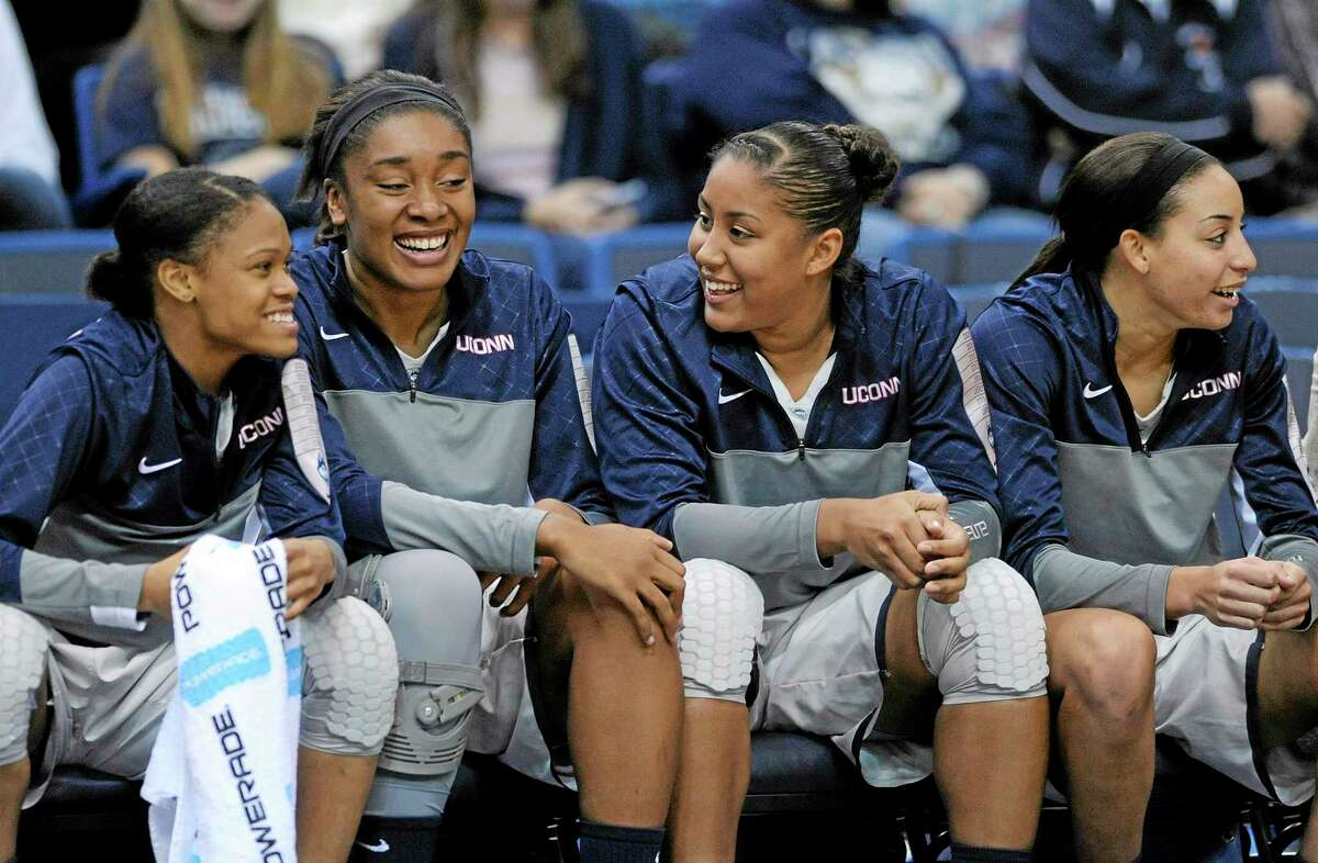 Injured UConn players Kaleena Mosqueda-Lewis, center left, and Morgan Tuck, center right, hope to be off the bench and helping their team on the court as soon as possible.