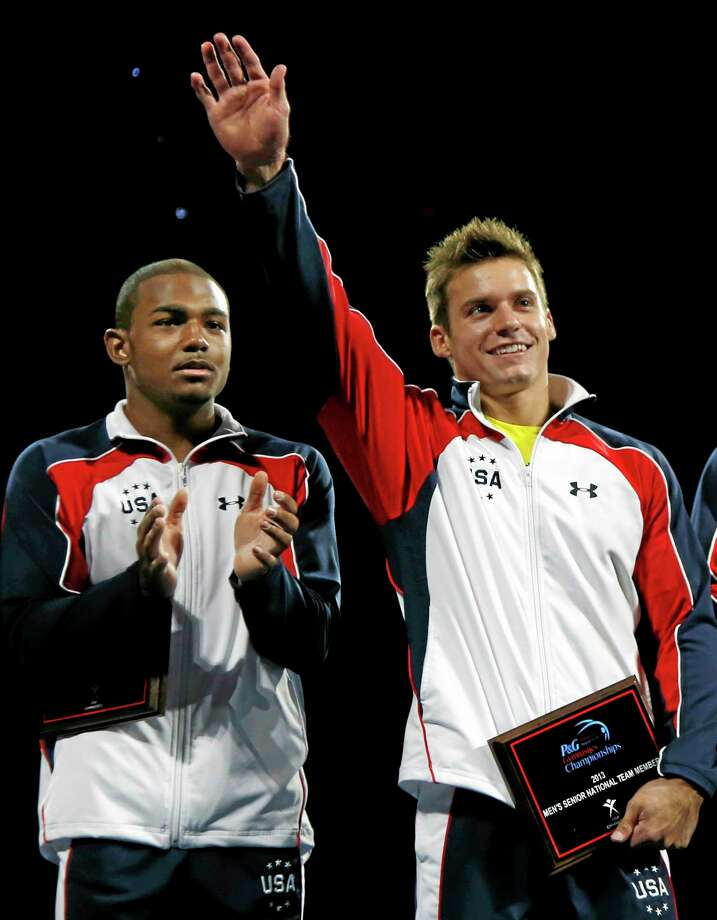 Sam Mikulak, right, acknowledges the crowd during the closing ceremony for the U.S. men's national gymnastics championships in Hartford on Sunday. Photo: Elise Amendola — The Associated Press  / AP