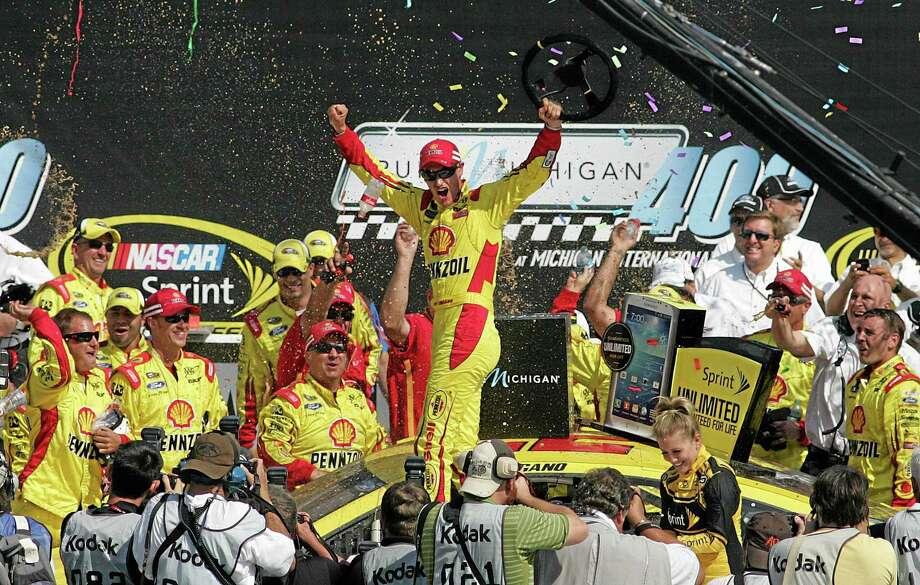 Joey Logano, center, celebrates after winning the NASCAR Sprint Cup series Pure Michigan 400 auto race at Michigan International Speedway in Brooklyn, Mich., Sunday, Aug. 18, 2013. (AP Photo/Luke Brodbeck) Photo: AP / AP