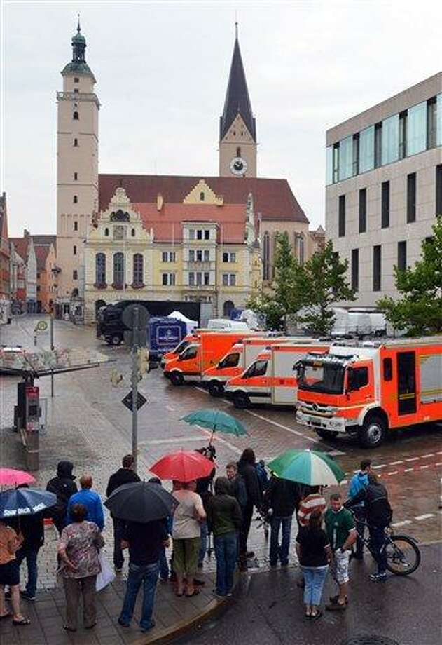 Onlookers stand in front of the city hall in Ingolstadt, Germany, Monday, Aug. 19, 2013, after a man has taken several hostages in the city hall of Ingolstadt. Police spokesman Guenther Beck said it wasn't clear what weapons the man might have or what he wants. The incident started shortly before 9 a.m. (0700 GMT) Monday and Beck said police were in contact with the man by telephone. (AP Photo/dpa, Peter Kneffel) Photo: AP / dpa