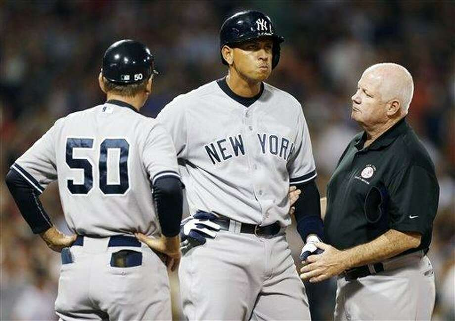 New York Yankees' Alex Rodriguez, center, is tended to by a trainer at first base after being hit by a pitch in the second inning of a baseball game against the Boston Red Sox in Boston, Sunday, Aug. 18, 2013. (AP Photo/Michael Dwyer) Photo: AP / AP