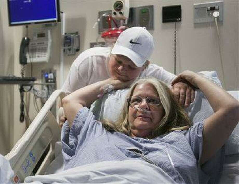 C.J. Saulsgiver, with his mother Christine Friday, March 22, 2013 in her hospital room. C.J. performed CPR on her saving her life after she suffered a heart attack. (AP Photo/Scott G. Winterton, Deseret News) Photo: AP / Deseret News