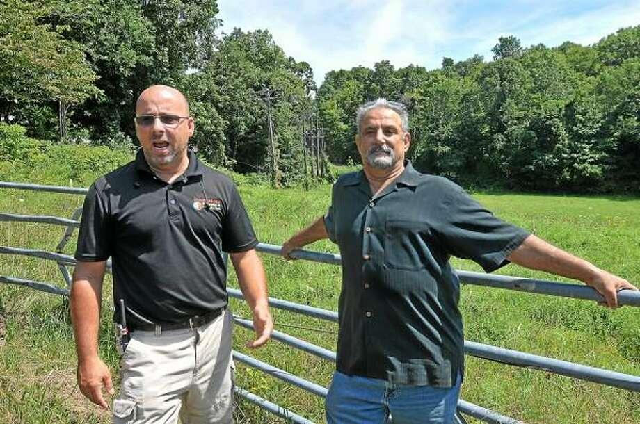 Sean Hayes, left, owner of Powder Ridge Mountain Park & Resort in Middlefield and investor, John Gramegna are frustrated with the lack of cooperation from CL&P and AT&T for the past nine months as contractors continue to work with generators. Hayes is currently waiting for 500 yards of power lines to be restored by the utility companies. Hayes has spent over $100,000 repairing and replacing utility poles on the property and completed the upgrade of 13 transformers because CL&P did not want to provide the same power voltage that was provided to the previous owners. Catherine Avalone - The Middletown Press / TheMiddletownPress