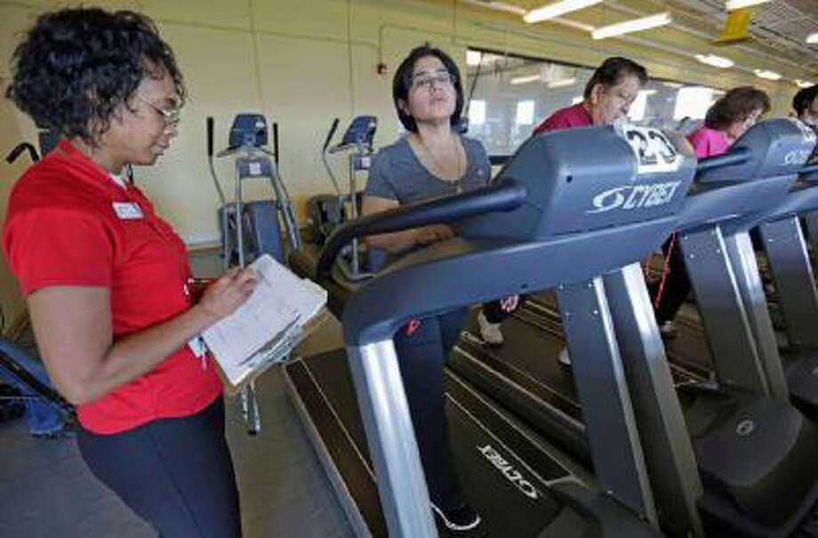 In this March 26, 2013 photo, Aidee Diaz, 36, center, exercises with personal trainer Angela Appleton, left, at the Rauner Family YMCA in Chicago. Diaz lost 100 pounds since a simultaneous robotic kidney transplant and obesity surgery.