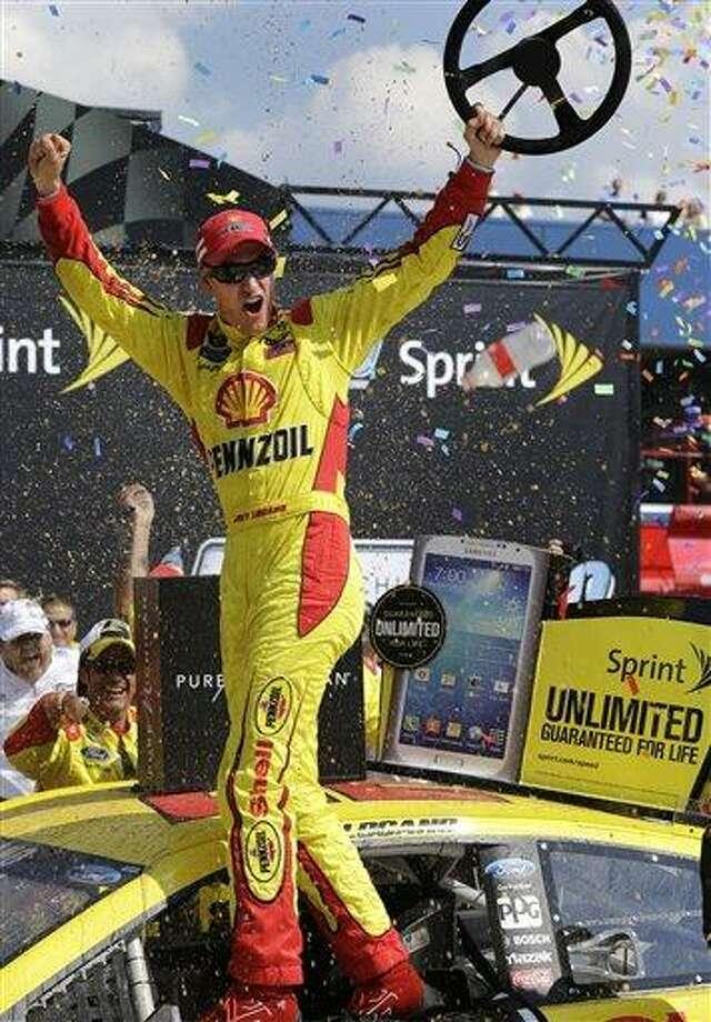Joey Logano celebrates winning the NASCAR Sprint Cup series Pure Michigan 400 auto race at Michigan International Speedway in Brooklyn, Mich., Sunday, Aug. 18, 2013. (AP Photo/Paul Sancya) Photo: AP / AP